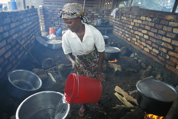 Tanzania Woman Pouring Water and Cooking