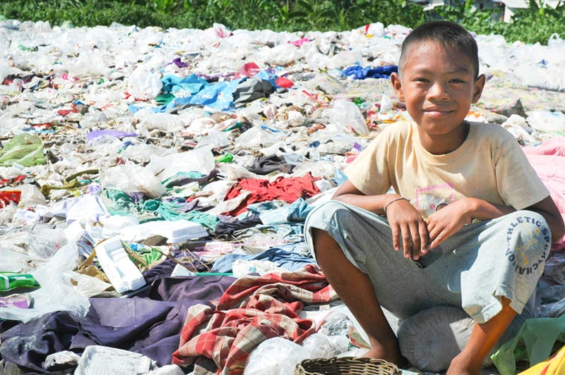 Thailand boy sitting on trash