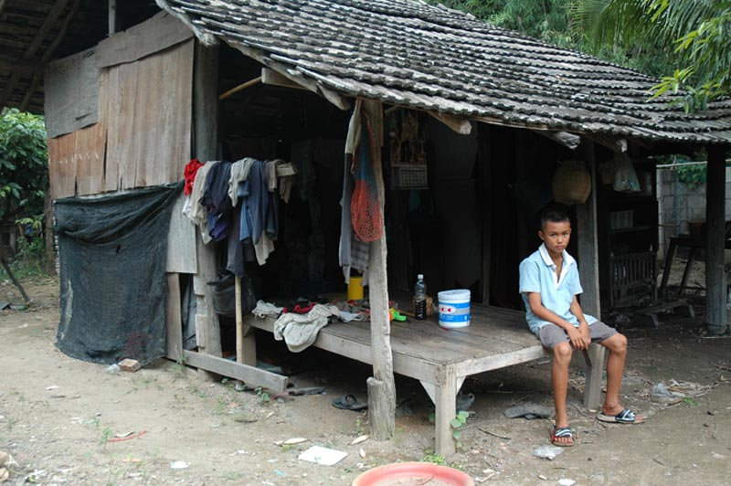 Thailand boy sitting outside home