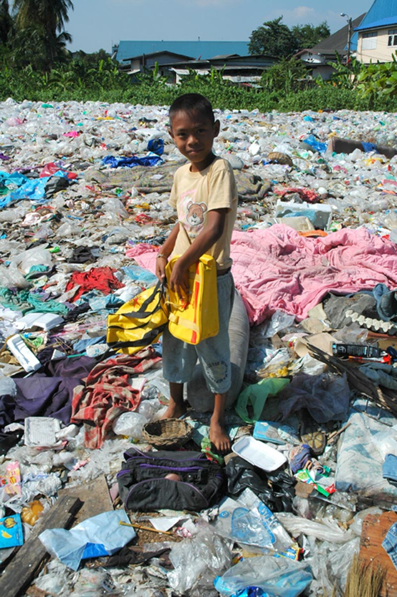 Thailand boy standing in trash