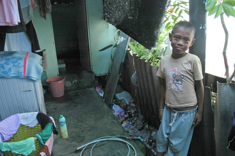 Thailand boy standing outside home