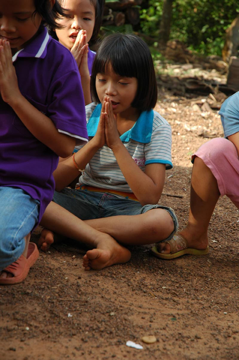 Thailand girl praying crosslegged