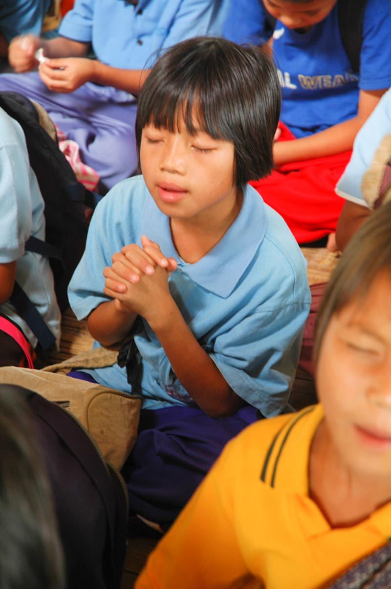 Thailand girl praying with others