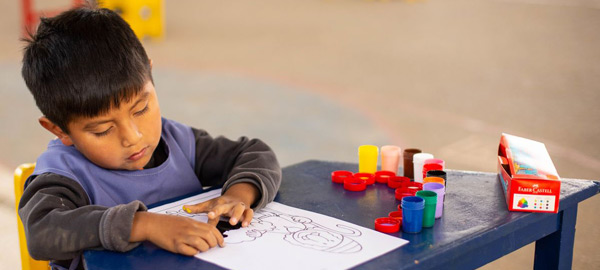 a young boy learning to finger paint