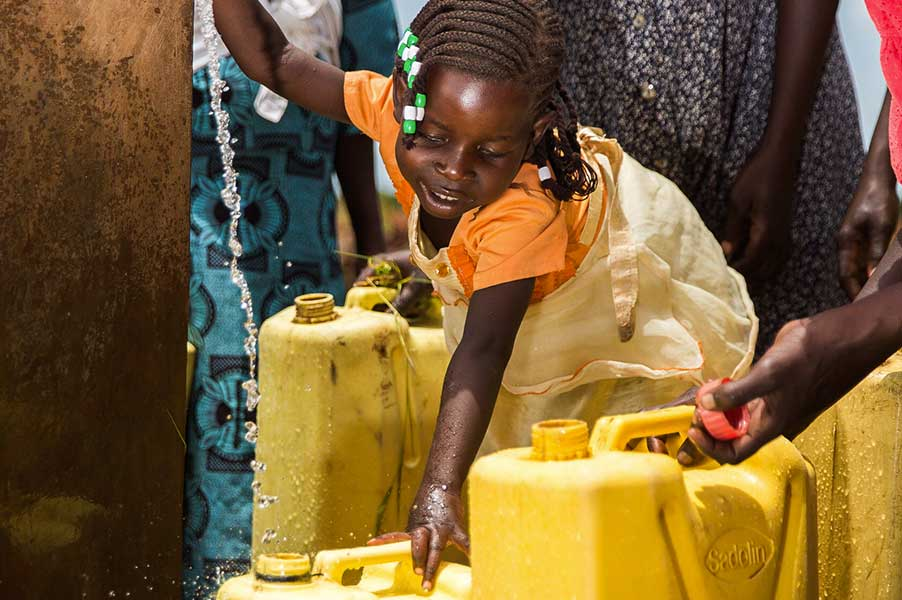 A young girl helps to fill water jugs