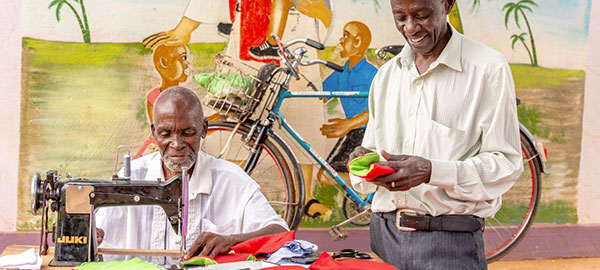 Two men sewing in front of a colorful mural