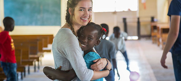 A young woman hugs a Compassion center child