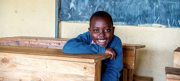 A boy sits at a school desk smiling
