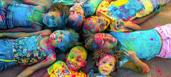 Kids lay in a circle laughing, covered in paint