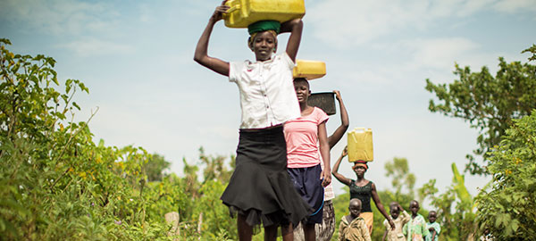 A group of children carry water jugs on their heads