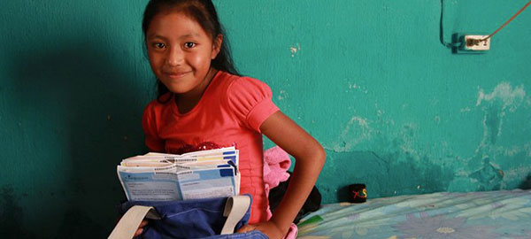 A young girl holds letters from a sponsor