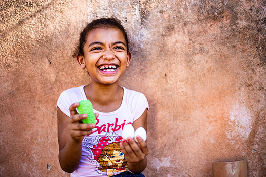 A laughing young girl wearing a Barbie t-shirt holds two eggs in one hand