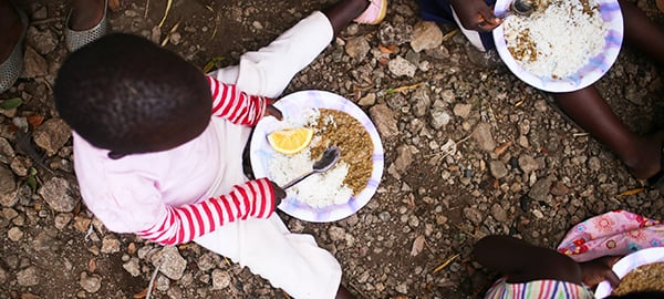 A child sits on the ground with a plate of food