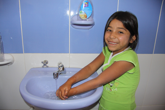 A young girl washes her hands in a sink while smiling