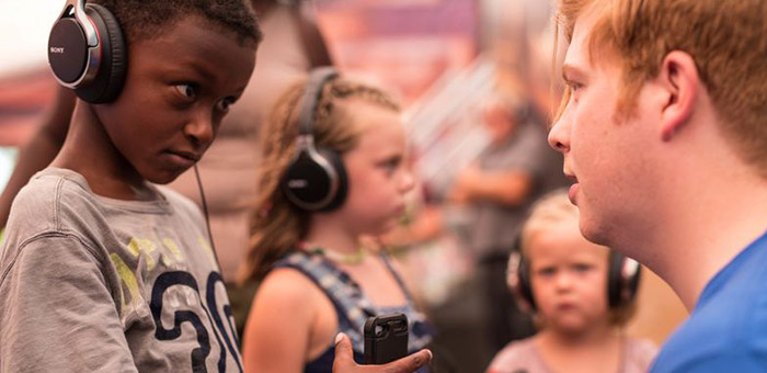 Young kids listening to the Compassion Experience on headphones