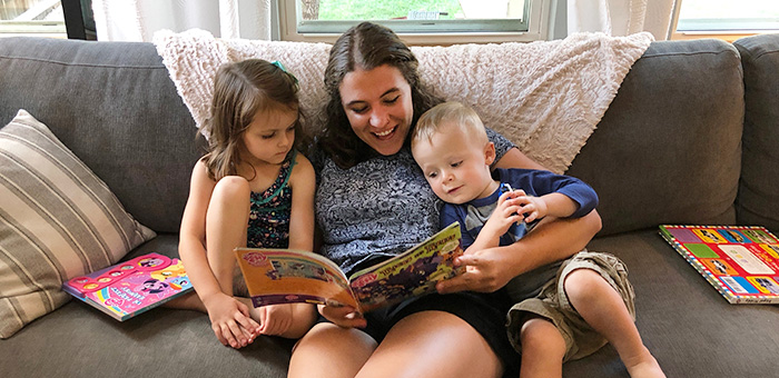 An intern reads to the children in the home she stays at