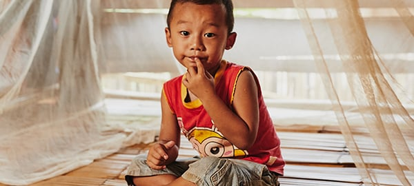 A boy sits in front of malaria prevention nets