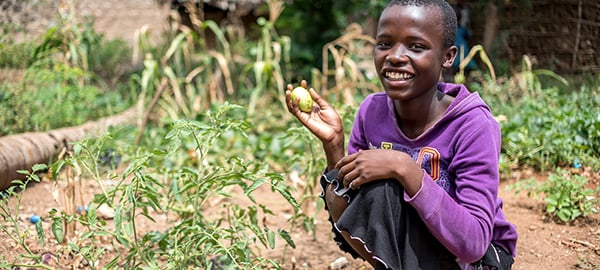 A child smiles while holding harvest in a garden