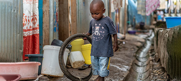 A boy playing with an old tire in the street
