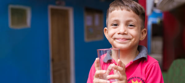 A boy holding a glass of clean safe water