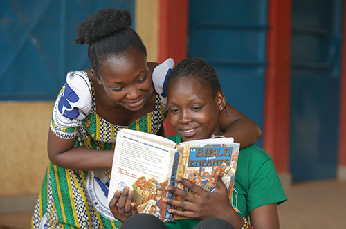 Two young girls read the Bible together