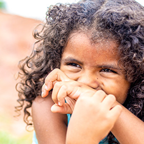 A young girl with curly hair covers her mouth with her wrist as she laughs