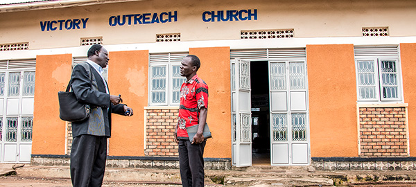 two men speaking to one another in front of a church