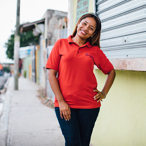 a woman in a red shirt stands with her head tilted