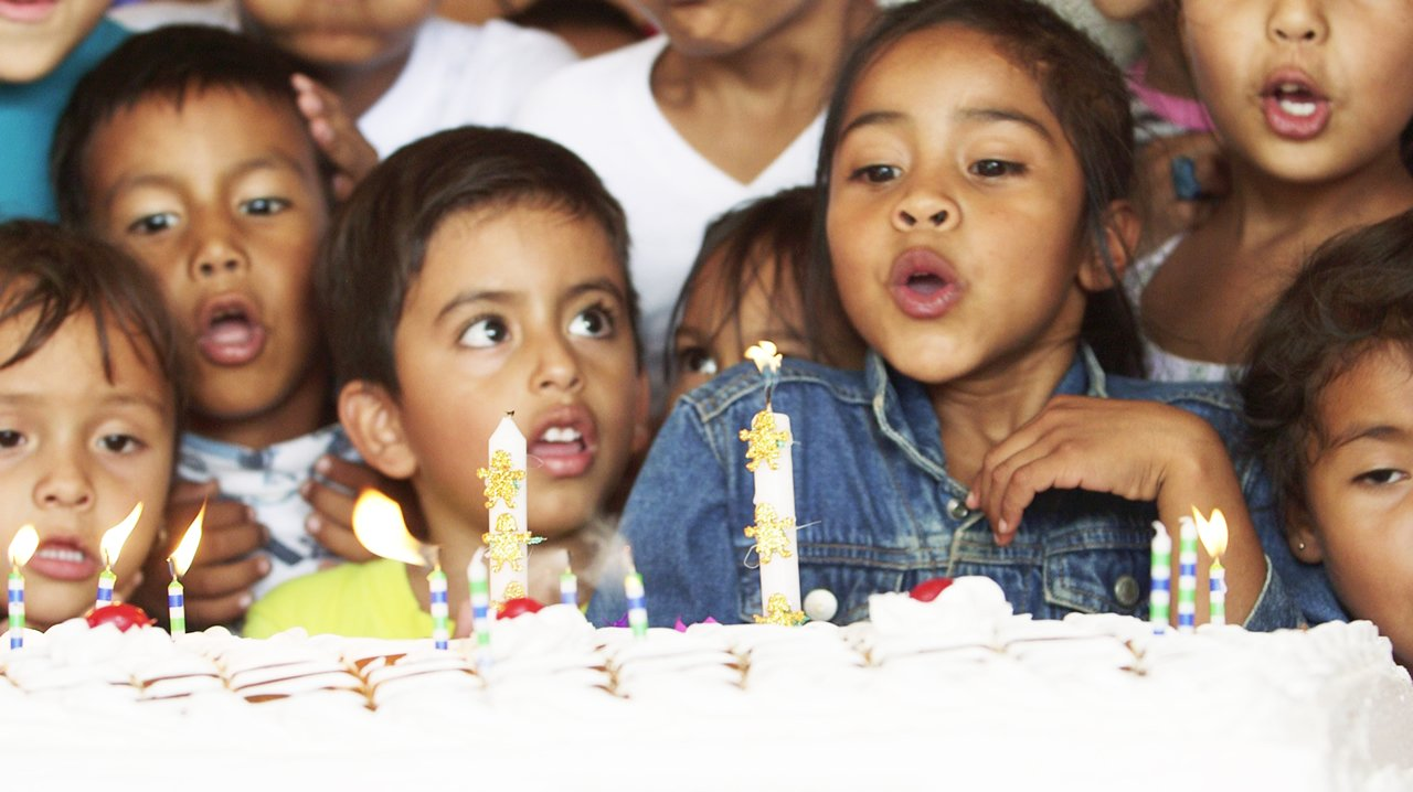 Girl blowing out a candle on a birthday cake surrounded by a group of children