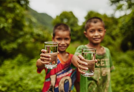 Two young boys showing you two cups of clean water.