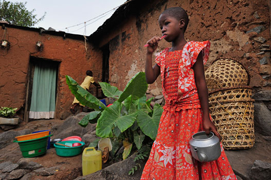 Nyabwiri holding a kettle in front of her home