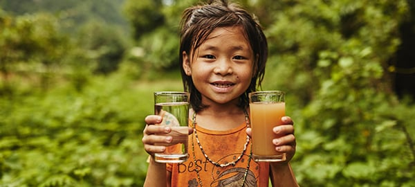A girl smiles and holds two glasses of water