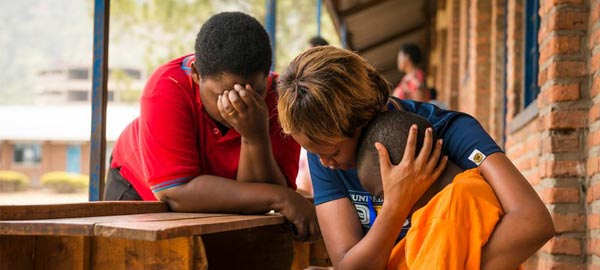 Sponsor embracing and praying for young boy