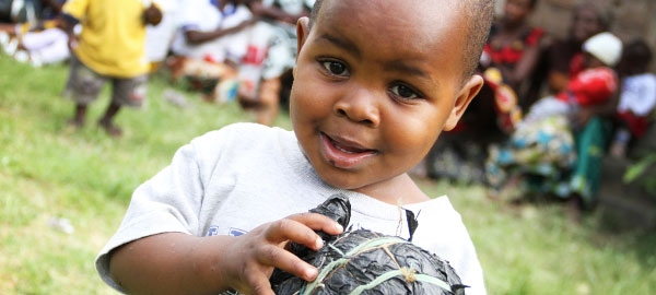 A young boy smiles while holding a ball