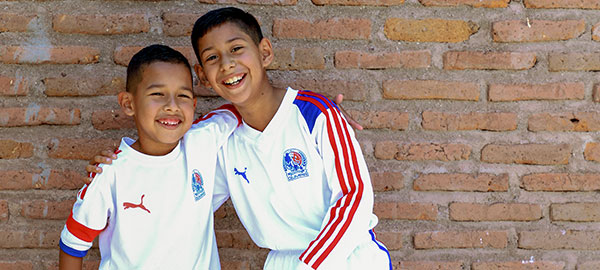 Two boys smile in soccer uniforms